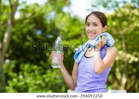 Woman with water bottle and towel after doing sport - stock photo