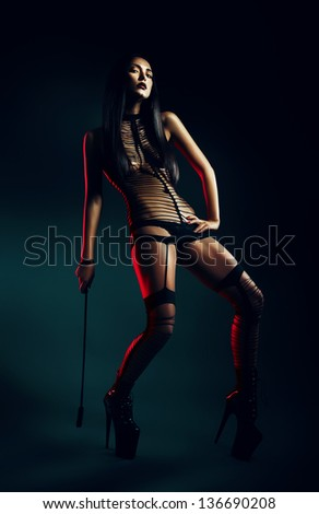woman with whip in red lihgt - stock photo