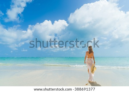 Woman with white clothe walking  on the beach