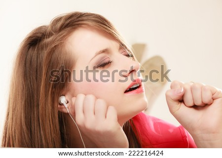 Woman with white headphones listening to music and singing a song. Student girl learning language with new technology. - stock photo
