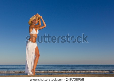 woman with white sarong on the beach - stock photo