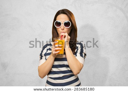 Woman with white sunglasses drinking a juice