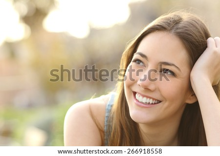 Woman with white teeth thinking and looking sideways in a park in summer - stock photo