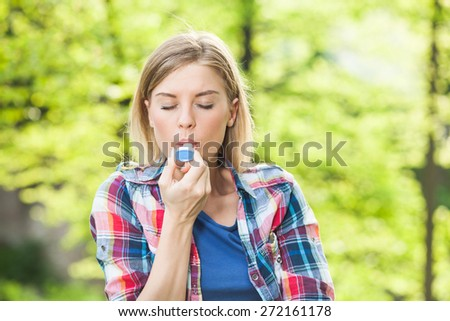 Woman with with allergy symptom using inhaler - stock photo