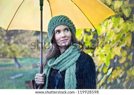 Woman with yellow umbrella smiling as raining - stock photo
