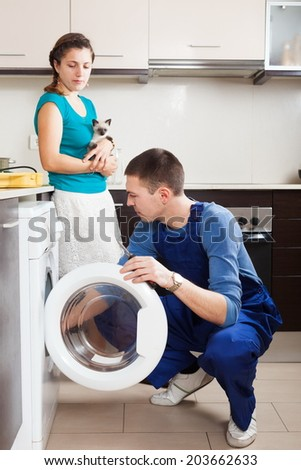 Woman with young Siamese kitten watches as worker repairs washing machine.