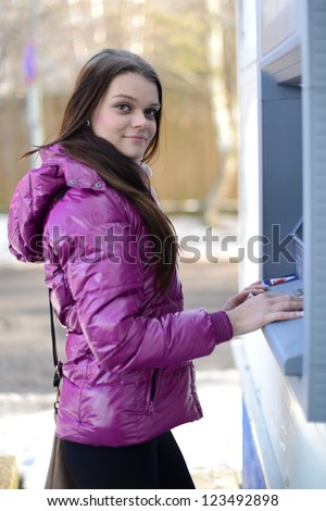 Woman withdrawing money from credit card at ATM. - stock photo