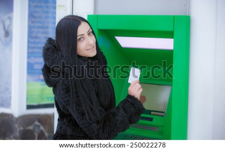 Woman withdrawing money from credit card at ATM  - stock photo