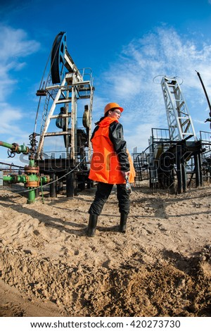 Woman worker in the oil field talking on the radio wearing red helmet and orange work clothes. Industrial site background.