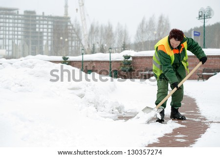 Woman worker in uniform shoveling snow after a storm - stock photo