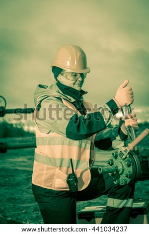 Woman worker on the oil field repairing of oil and gas well, with the wrench wearing  helmet and work clothes. Working process on oil wellhead. Toned sepia.