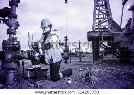 Woman worker on the oil field repairing of oil and gas well, with the wrench wearing  helmet and work clothes. Working process on oil wellhead.