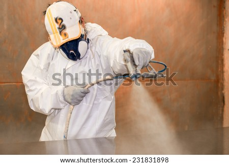 Woman worker painting wooden board with spray. - stock photo