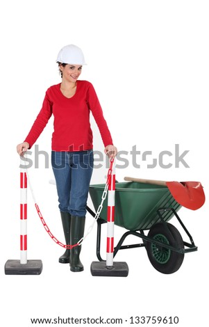 Woman worker with a wheelbarrow and barrier - stock photo