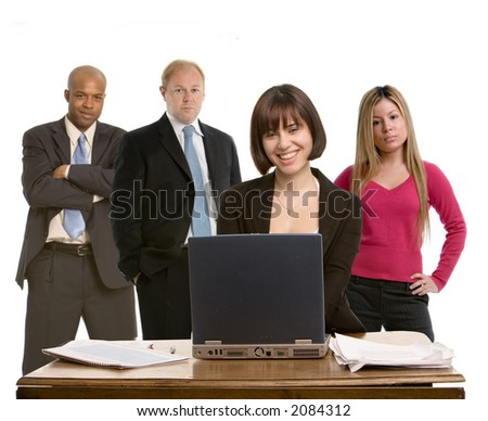 Woman working at a computer with colleagues in background