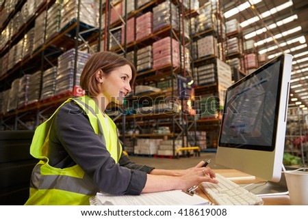 Woman working at computer in on-site office of a warehouse