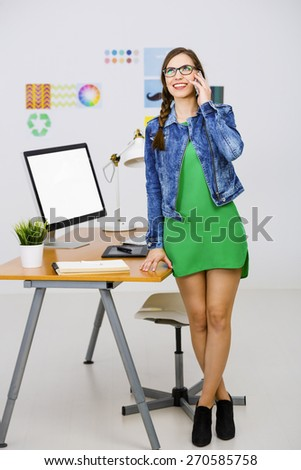 Woman working at desk In a creative office, making a call  - stock photo