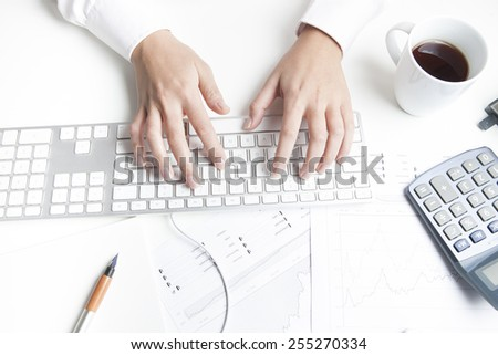 Woman working at desk, keyboard - stock photo