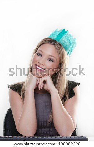 woman working at her desk wearing a christmas hat from a cracker  looking  happy