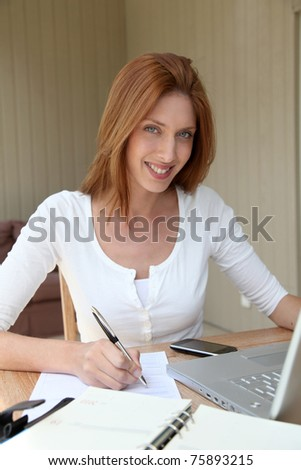 Woman working at home on laptop computer - stock photo
