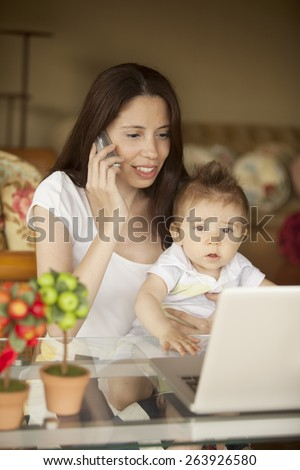 Woman working at home with baby - stock photo