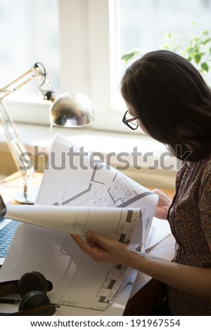 Woman working at home with laptop and architecture plan