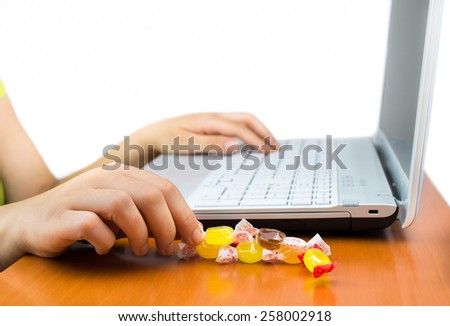 woman working at the laptop eating a candy sweet - stock photo