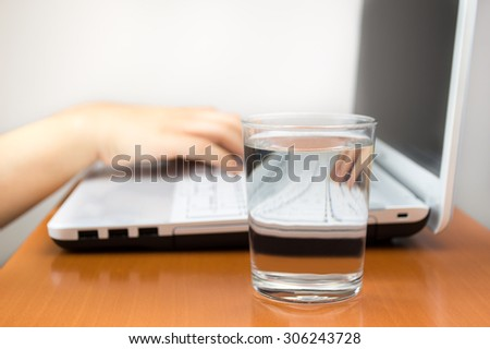 woman working at the laptop with a water glass to drink - stock photo