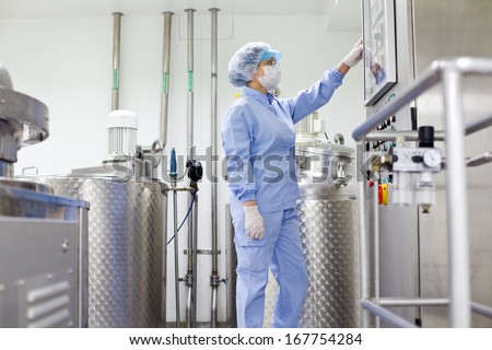 Woman working at the pharmaceutical factory. Shallow DOFF and 'high key' effect. See more images and video from this series.  - stock photo