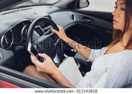 Woman working at the wheel in the car. don't text and drive - stock photo