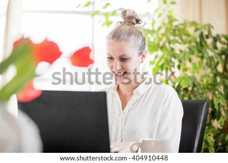 Woman working from home on her table with green flowers - stock photo