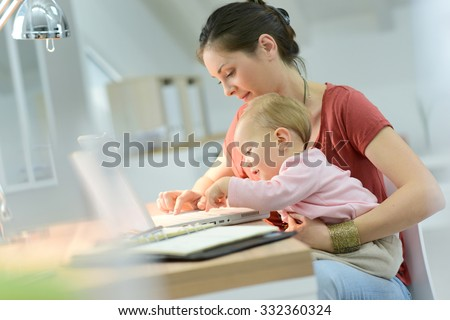 Woman working from home with baby on lap - stock photo