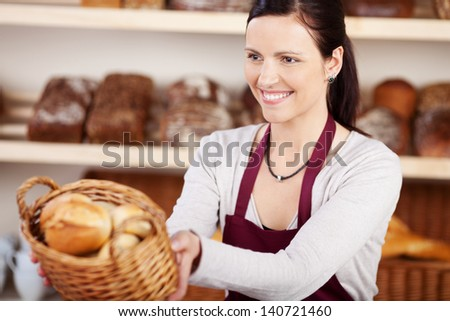 Woman working in a bakery offering a customer a basket of assorted bread and rolls with a friendly smile, focus to the woman - stock photo