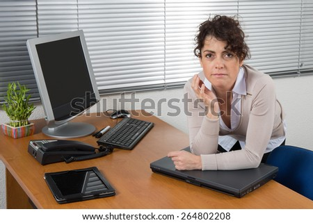 Woman working in a creative office and smiling at camera at her desk with computer - stock photo