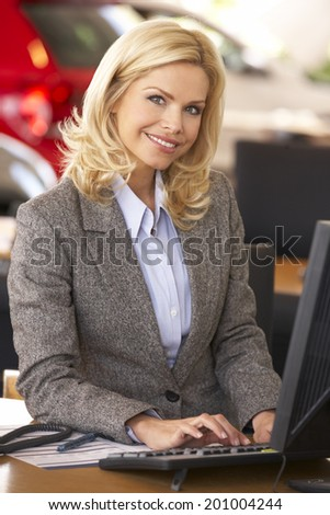 Woman working in car showroom