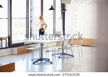 Woman working in empty meeting room - stock photo