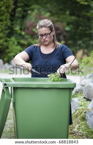 Woman working in her garden preparing for autumn - stock photo