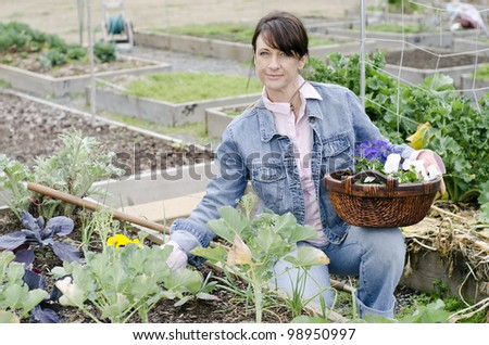woman working in her garden with a basket of flowers