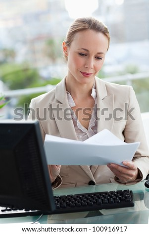 Woman working in her office with city view in background