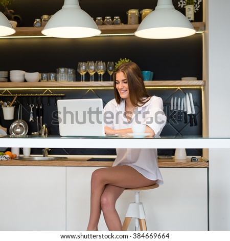 Woman working on a laptop at home in the morning. - stock photo