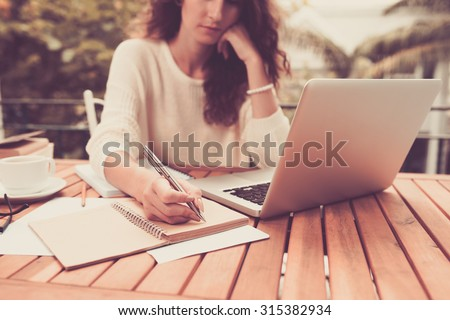 Woman working on computer and writing down her thoughts - stock photo