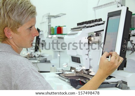 Woman working on computerized machine embroidery - stock photo