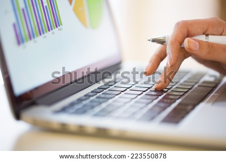 Woman working on financial data with computer - stock photo