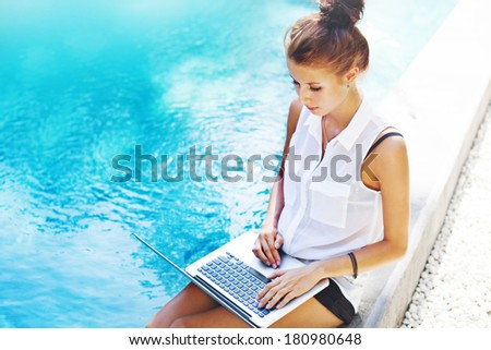 Woman working on her laptop computer sitting at poolside - stock photo