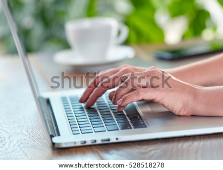 Woman working on her laptop computer. Working on laptop at home or office concept. Shallow DOF