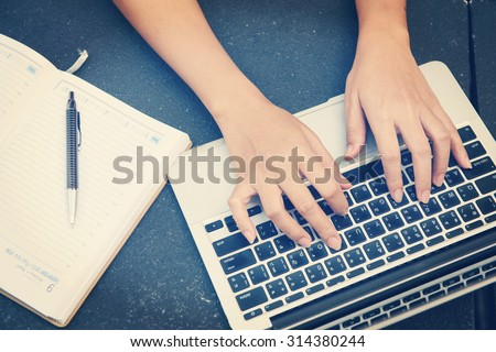 Woman working on laptop and writing, top view - stock photo
