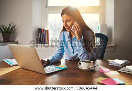 Woman working on laptop at office while talking on phone, backlit warm light - stock photo