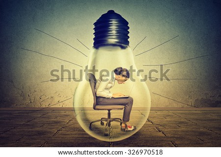 Woman working on laptop computer sitting inside electric light bulb isolated on gray office wall background  - stock photo