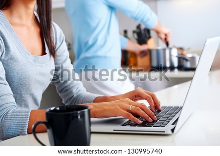 woman working on laptop in kitchen as boyfriend prepares meal. happy healthy relationship multiracial couple