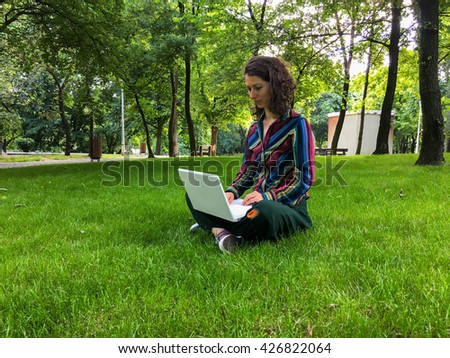 Woman working on laptop in park. Business woman working outside. Young woman working on laptop in nature. Beautiful woman working on electronic device - stock photo